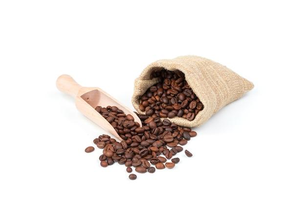 Rovesciare i chicchi di caffè da un sacchetto di lino e una spatola di legno su uno sfondo bianco.
