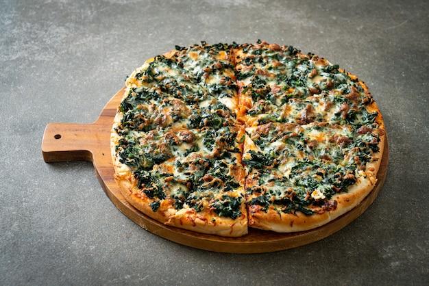 Pizza spinaci e formaggio su vassoio in legno - stile vegano e vegetariano
