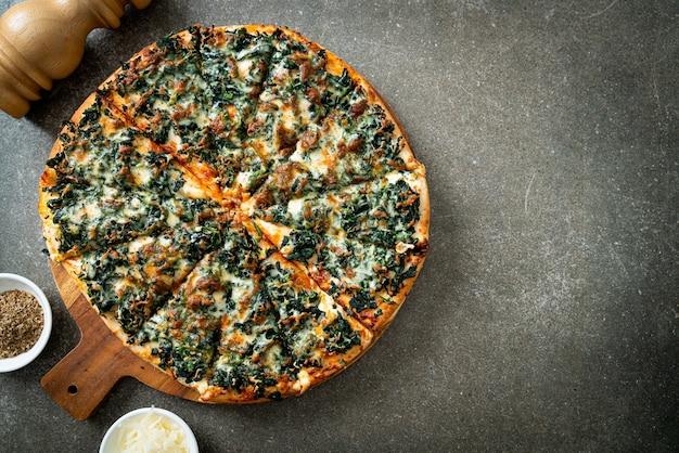 Pizza spinaci e formaggio su vassoio di legno - stile vegano e vegetariano