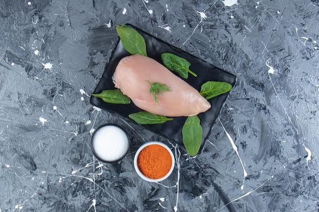 Spinaci e petto di pollo su un vassoio accanto a ciotole di sale e spezie, sulla superficie di marmo.