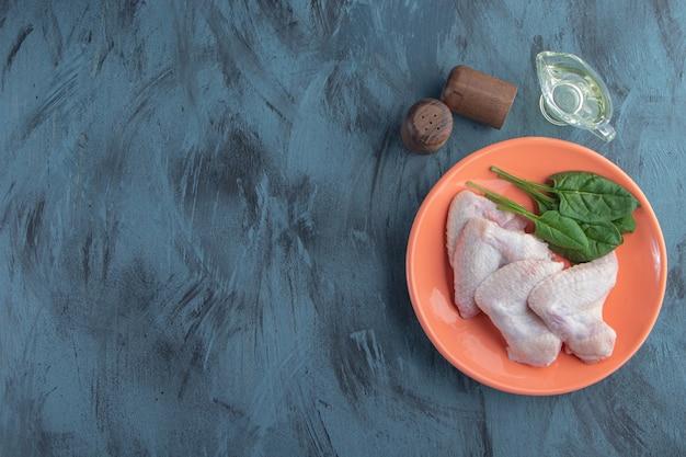 Spinaci e ala di pollo su un piatto accanto a fette di pepe e ciotola di olio, su sfondo blu.