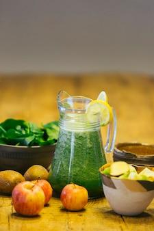 Spremuta a freddo di spinaci in un barattolo circondato dagli ingredienti utilizzati