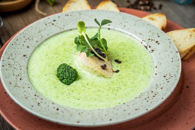 Zuppa di crema di spinaci nella ciotola sul tavolo rustico bianco, vista dall'alto, patè, foie gras