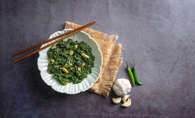 Curry di spinaci in ciotola bianca su piastrella di ardesia nera con uno strato vintage bacchette spicchio d'aglio e peperoncini vista dall'alto