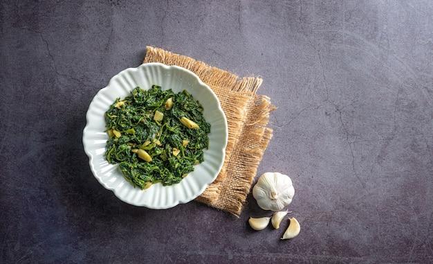 Curry di spinaci in ciotola bianca su piastrella di ardesia nera con uno strato vintage e vista dall'alto di spicchio d'aglio