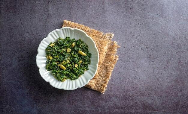 Curry di spinaci in ciotola bianca su piastrella di ardesia nera con vista dall'alto di uno strato vintage