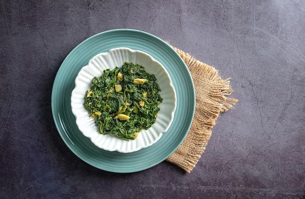 Curry di spinaci in ciotola bianca e piatto blu su piastrella di ardesia nera con vista dall'alto di uno strato vintage