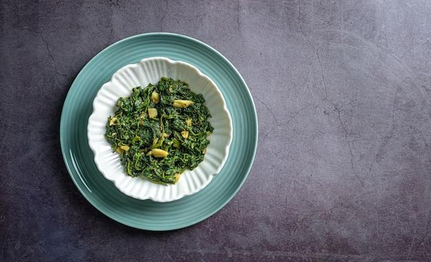 Curry di spinaci in ciotola bianca e piatto blu su vista dall'alto di ardesia nera