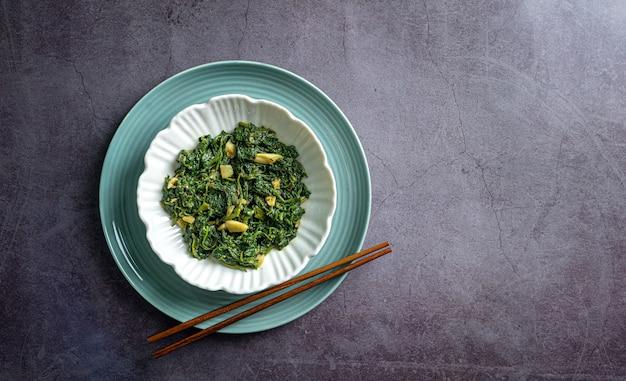 Curry di spinaci in ciotola bianca e piatto blu con bacchette su piastrelle di ardesia nera vista dall'alto
