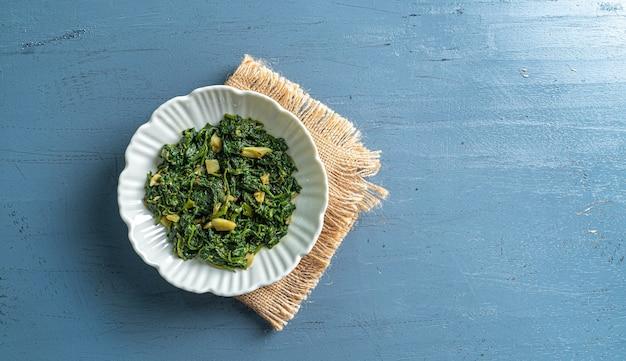 Curry di spinaci in ciotola bianca su tavolo di legno blu con vista dall'alto di uno strato vintage