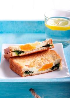 Spinaci e uova alla griglia panino, affettato sulla piastra