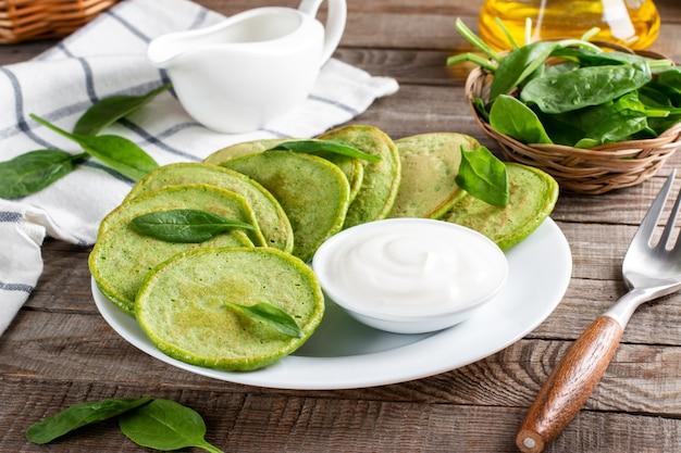 Frittelle di spinaci con foglie di spinaci e panna acida su un tavolo di legno