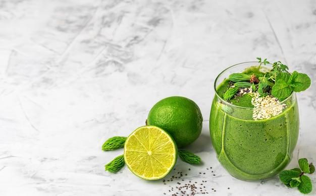 Frullato di spinaci con banana, lime, chia e semi di sesamo e microgreens in un bicchiere di vetro