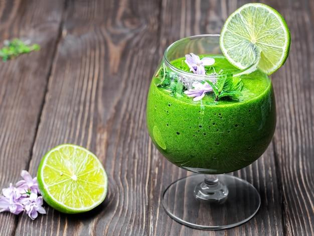 Frullato di spinaci con frutta e semi, decorato con foglie di menta, una fetta di lime e fiori di campo in un bicchiere di vetro