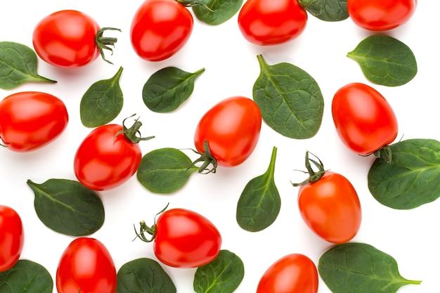 Spinaci e pomodori modellano la superficie su bianco. vista dall'alto