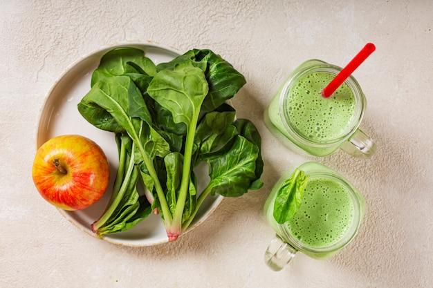 Frullato di spinaci e yogurt con mela. foglie succose degli spinaci e mela rossa matura. mangiare sano