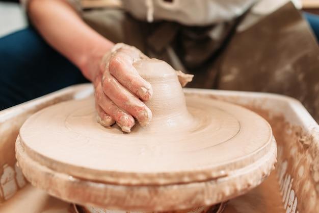 Ruota del vasaio di filatura con argilla e mano su di esso