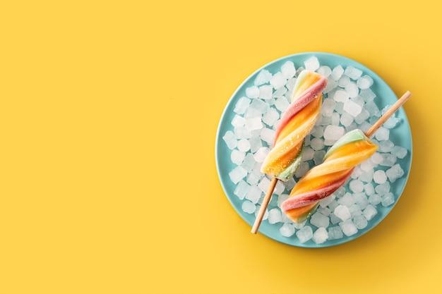 Ghiacciolo colorato a spirale con frutta su giallo
