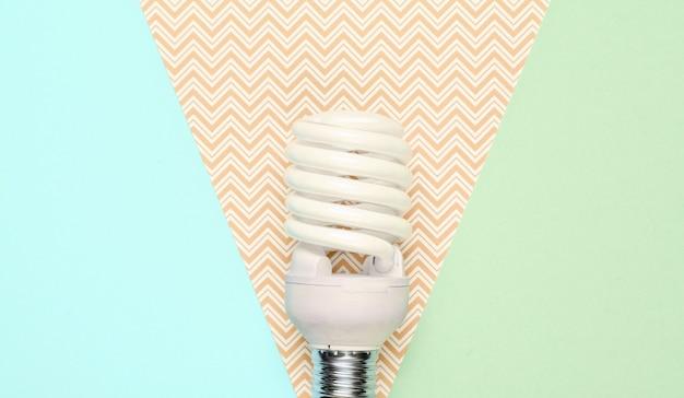 Lampadina a risparmio energetico a spirale su sfondo di carta pastello. vista dall'alto