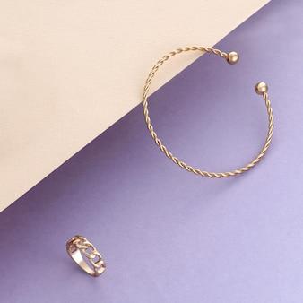 Bracciale moderno a forma di spirale e anello a forma di catena su sfondo beige e viola