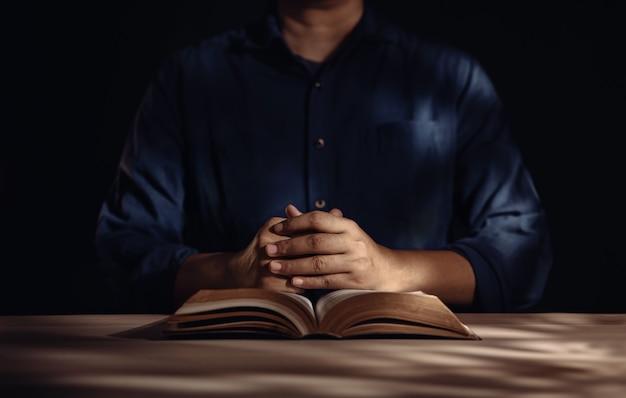 Spiritualità e concetto di religione, persona seduta sulla scrivania per pregare su una sacra bibbia in chiesa o in casa. credere e fede per il popolo cristiano