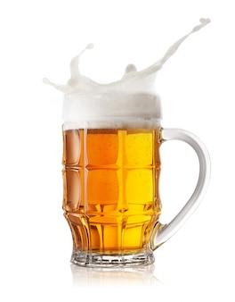 Spruzzata di schiuma in un boccale di birra sfaccettato