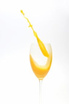 Spruzzata di succo d'arancia nel bicchiere su bianco