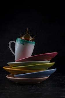 Spruzzi e schizzi da un pezzo di zucchero in una tazza con caffè su sfondo nero.