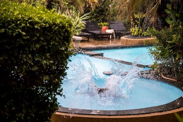 Spruzzi d'acqua dopo essersi tuffati in una piscina tropicale all'aperto sotto la pioggia battente