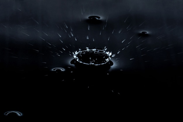 Spruzzata di una goccia d'acqua su uno sfondo nero