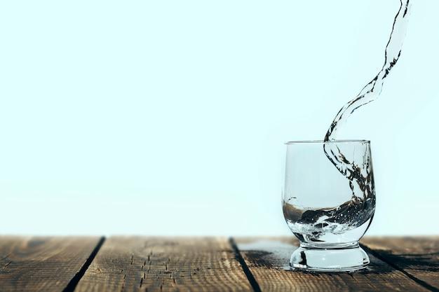 Spruzzata d'acqua in un bicchiere su legno