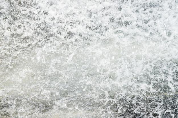 Spruzzi di acqua limpida. sfondo naturale e consistenza. fontana rinfrescante nel parco nella calura estiva.