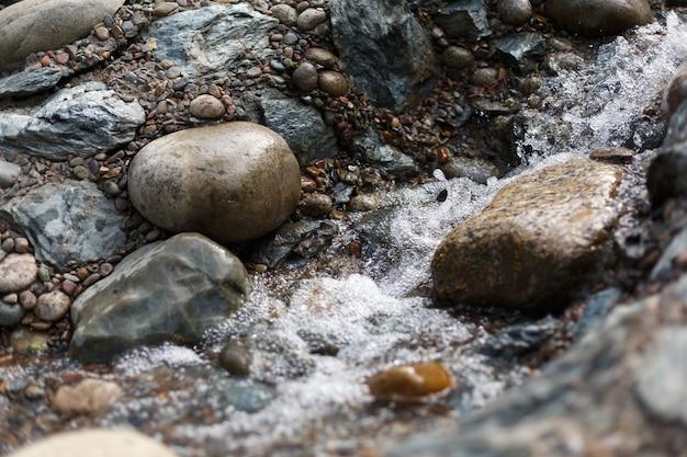 Schizzi e gocce di ruscello in esecuzione su pietre nel giardino giapponese