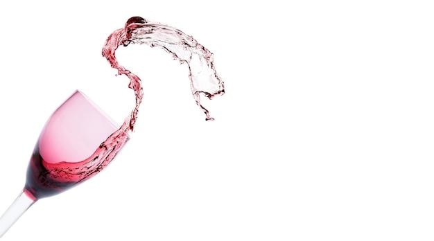 Spruzzi di vino rosso dal bicchiere di cristallo