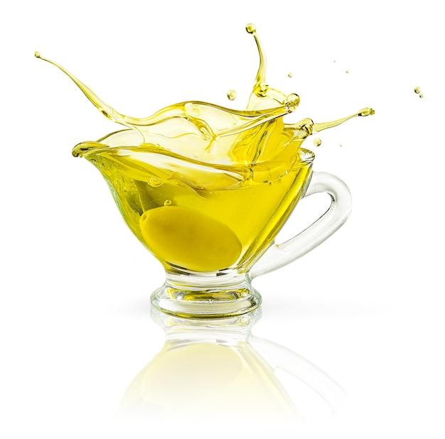 Spruzzi di olio d'oliva in barattolo trasparente isolato su superficie bianca con tracciato di ritaglio.