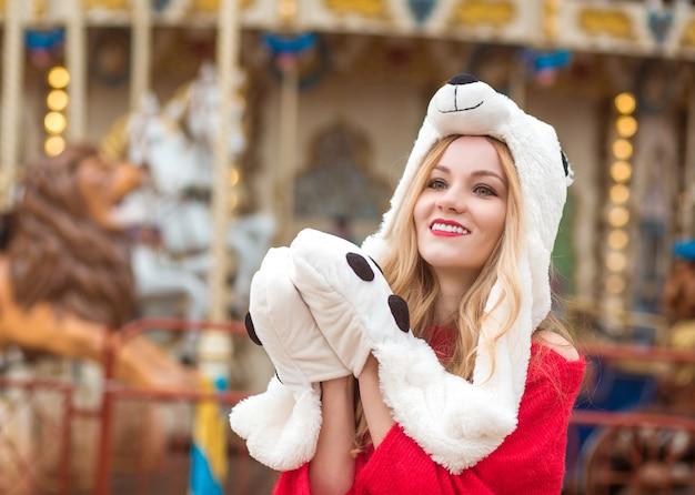 Splendida donna bionda che indossa un maglione lavorato a maglia rosso e un cappello divertente, in posa sullo sfondo della giostra con luci