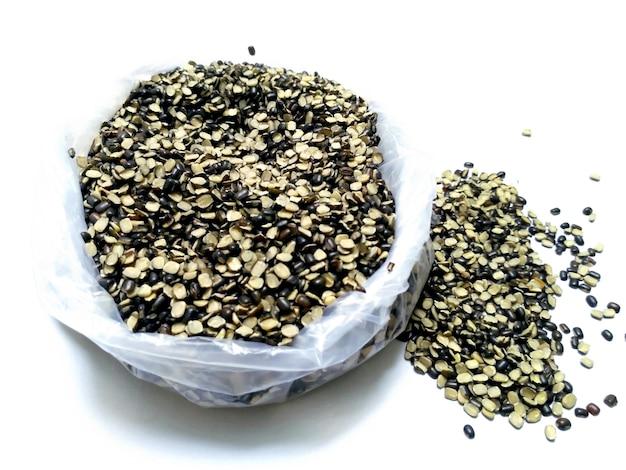 Lenticchie nere spaccate conosciute anche come grammo nero, urad dal nero, vigna mungo, fagiolo urad, urad dal, minapa pappu, fagiolo mungo o fagiolo matpe nero isolato su sfondo bianco