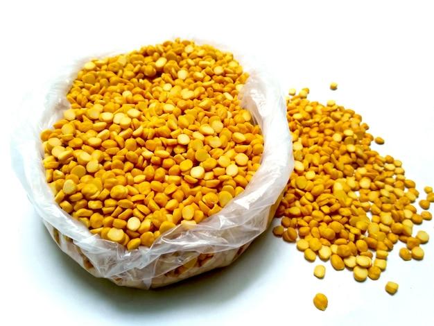 Ceci spaccati anche conosciuti come chana dal, piselli spezzati chana gialli, lenticchie di ceci essiccate o toor dal isolati su sfondo bianco