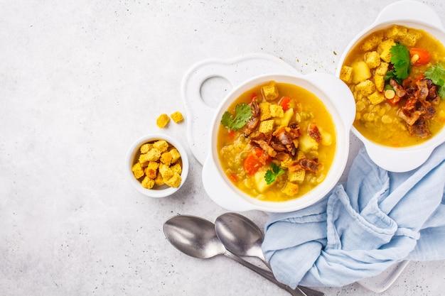 Zuppa di piselli spezzati con pancetta affumicata e cracker in un piatto bianco, copia dello spazio.