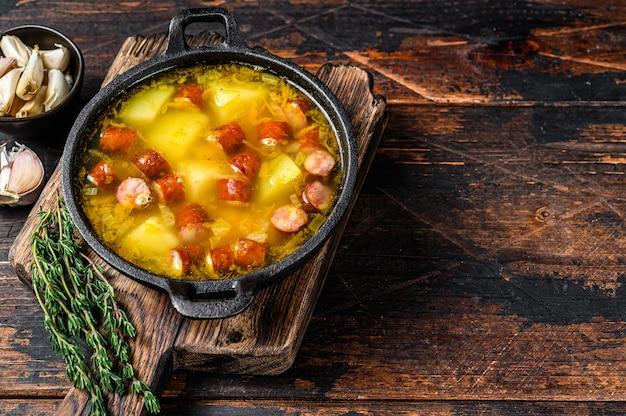 Zuppa di piselli spezzati con salsicce affumicate in padella. fondo in legno scuro. vista dall'alto. copia spazio.