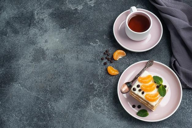 Strati di pan di spagna con crema al burro, decorati con fette di cioccolato al mandarino e menta. delizioso dessert dolce per il tè. vista dall'alto, copia dello spazio.