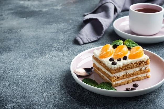 Strati di pan di spagna con crema al burro, decorati con fettine di cioccolato al mandarino e menta. delizioso dessert dolce per il tè. vista dall'alto, copia dello spazio.