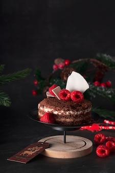 Pan di spagna tre cioccolatini in una decorazione di festa di capodanno con lamponi. su sfondo scuro
