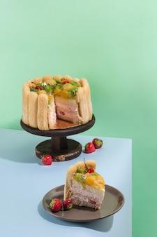 Pan di spagna con kiwi, pesche e ciliegie su supporto di legno, un pezzo di torta su un piatto