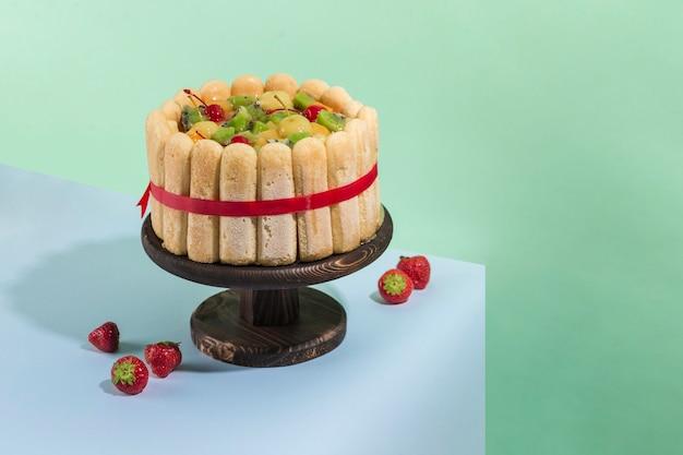 Pan di spagna con kiwi, pesche e ciliegie su supporto in legno con fragole