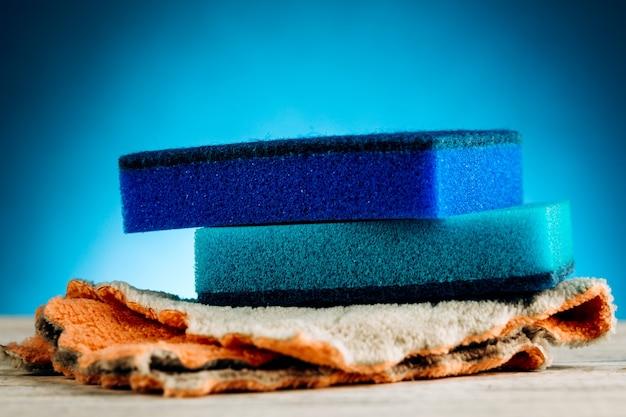 Spugna per lavare i piatti su sfondo blu.