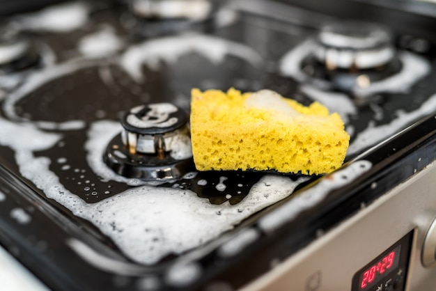 Spugna con schiuma sul fornello a gas sporco per la pulizia. una casa pulita è uno stile di vita sano