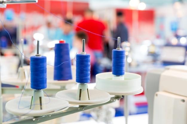 Bobine di fili blu sulla macchina da cucire, primo piano. fabbrica di tessuti, tessitura, produzione tessile, industria dell'abbigliamento