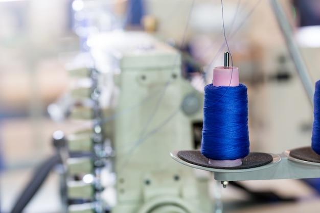 Bobine di fili blu sulla macchina da cucire, fabbrica