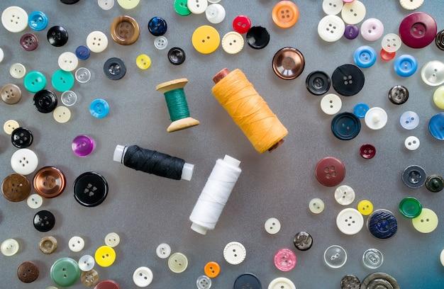 Bobine di filo colorato giacciono al centro del tavolo circondate da vecchi bottoni di plastica colorati. vista dall'alto